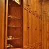 This Walk-In closet made from Red Oak and Natural Maple interiors features matching paneled walls, drawer base cabinets, roll out hampers, plenty of clothes hanging space, adjustable shelving and shoe cubbies.Also, a full length mirror, open glass shelf cabinet & pull out folding area.